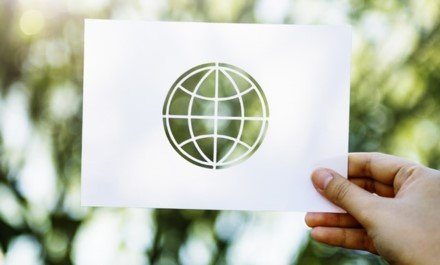 Hand holding card with world symbol cutout of center held up to a green background dappled with light