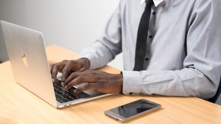 Man in grey shirt and black tie typing on a mac laptop with cell phone sitting on table next to computer